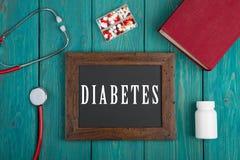 Quadro-negro com texto & x22; Diabetes& x22; , estetoscópio, comprimidos e livro no fundo de madeira azul foto de stock