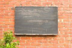 Quadro-negro envelhecido na parede de tijolo vermelho. Fotos de Stock