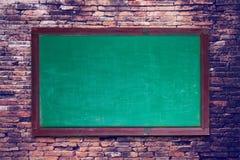quadro-negro no fundo velho da parede de tijolo Foto de Stock
