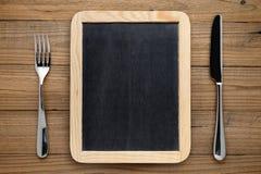Quadro-negro para o menu, a forquilha e a faca na tabela Fotografia de Stock Royalty Free