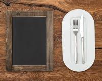 Quadro-negro para o menu na tabela de madeira Fotos de Stock Royalty Free