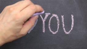 Quadro-negro pequeno com o texto eu te amo escrito nele no giz Curso ao longo do contorno com giz video estoque