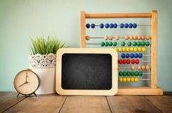 Quadro-negro, pilha de ábaco frisado colorido e pulso de disparo De volta ao conceito da escola Imagem de Stock