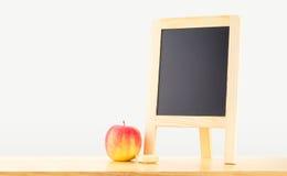 Quadro-negro vazio com a maçã vermelha na tabela de madeira no fundo cinzento Imagem de Stock Royalty Free