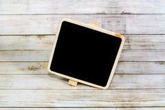 Quadro-negro vazio no fundo de madeira Fotos de Stock