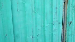 Quadro no movimento ao longo da cerca quebrada verde e cinzenta da construção do metal filme