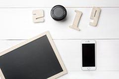 Quadro ou quadro-negro e telefone celular vazio pequeno e dígitos de madeira do entalhe que formam o número do ano novo 2019 com  imagem de stock