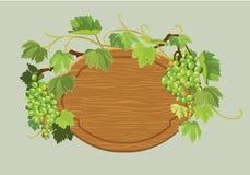 Quadro oval de madeira com uvas e as folhas verdes no bege Fotos de Stock Royalty Free