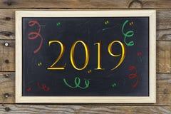 Quadro preto com o ano novo 2019 e confetes coloridos foto de stock