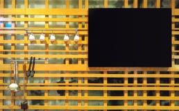 Quadro preto vazio que pendura na parede de madeira criativa com Kitchenware Fotografia de Stock