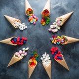 Quadro redondo de doces sortidos brilhantes coloridos em cones do waffle Configuração lisa, vista superior Foto de Stock Royalty Free