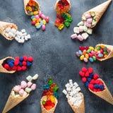 Quadro redondo de doces sortidos brilhantes coloridos em cones do waffle no fundo escuro Configuração lisa, vista superior Fotos de Stock Royalty Free