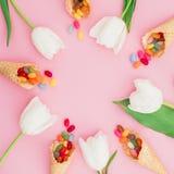 Quadro redondo feito de doces brilhantes coloridos em cones do waffle e em flores das tulipas no fundo cor-de-rosa Configuração l Imagens de Stock Royalty Free