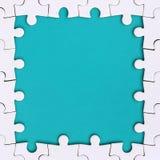 Quadro sob a forma de um retângulo, feito de um enigma de serra de vaivém branco em torno do espaço azul fotos de stock royalty free