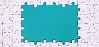 Quadro sob a forma de um retângulo, feito de um enigma de serra de vaivém branco em torno do espaço azul imagens de stock