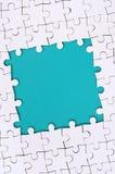 Quadro sob a forma de um retângulo, feito de um enigma de serra de vaivém branco em torno do espaço azul imagem de stock royalty free