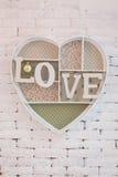 Quadro sob a forma do coração contra uma parede de tijolo Foto de Stock