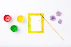 Quadro vazio com escova, pintura e flores no fundo branco Foto de Stock Royalty Free