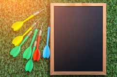Quadro vazio com a seta colorida do dardo no assoalho da grama jpg Imagens de Stock Royalty Free