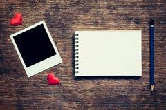 Quadro vazio da foto, caderno, lápis e coração vermelho na tabela de madeira Fotografia de Stock Royalty Free