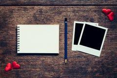 Quadro vazio da foto, caderno, lápis e coração vermelho na tabela de madeira Foto de Stock
