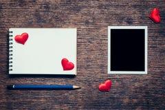 Quadro vazio da foto, caderno, lápis e coração vermelho na tabela de madeira Foto de Stock Royalty Free