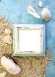 Quadro vazio da foto com escudos do mar na areia sobre o papel azul Curso, conceito das férias da praia imagem de stock royalty free