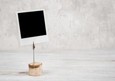 Quadro vazio da foto do modelo na tabela de madeira contra a parede do vintage fotos de stock