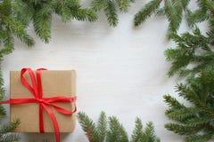 Quadro verde dos ramos de árvore do abeto no fundo de madeira branco, caixa de presente com a fita vermelha do cetim, cartão de N foto de stock royalty free