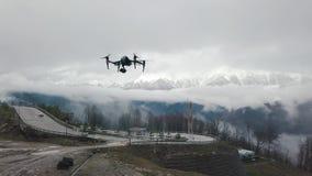 quadrocopter在路的寄生虫飞行特写镜头有在白色雾和雪的山的在背景 股票 股票视频