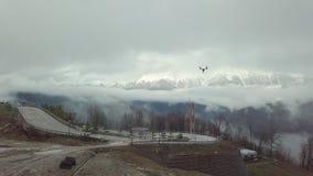 quadrocopter在路的寄生虫飞行特写镜头有在白色雾和雪的山的在背景 股票 股票录像