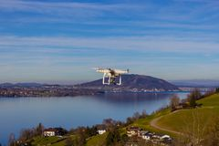 A quadrocopter in the air in front of a lake in Austria. A quadrocopter after starting its flight, in background a lake in Austria stock photo