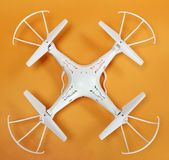 Quadrocopter bianco su una vista superiore del fondo arancio luminoso fotografia stock