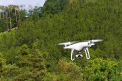Quadrocopter branco do zangão com a câmera que voa sobre a floresta verde foto de stock