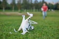 Quadrocopter brisé en parc Dommages de propulseur Opérateur courant sur le fond Images stock