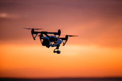 Quadrocopter-Brummen mit Fernbedienung Dunkles Schattenbild gegen colorfull Sonnenuntergang Weicher Fokus Getontes Bild lizenzfreies stockbild