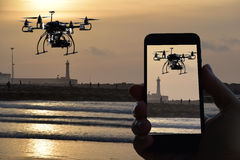 Quadrocopter del abejón, teledirigido del smartphone, puesta del sol sobre el fondo de la atalaya de la pizca del mar Imágenes de archivo libres de regalías