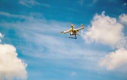 Quadrocopter del abej?n del vuelo en el cielo y las nubes foto de archivo libre de regalías
