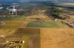 Quadrocopter die over landbouwgrond vliegen Stock Fotografie
