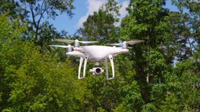 Quadrocopter drone with the camera. Modern RC Drone. Copter flying against green blurred background. stock photo