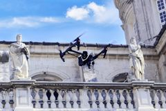 Quadrocopter drone in flight is shooting landmarks in the center of the old European city. Stock Photo