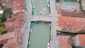 Quadrocopter está volando sobre sorprender el pequeño canal del mar en Venecia en d3ia, barcos y los yates están flotando metrajes