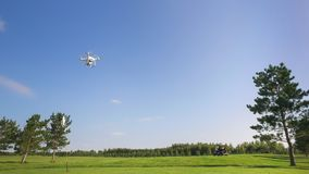 Quadrocopter Flies for Golf Cart on a Golf Course. Quadrocopter Flies for Golf Cart on a Golf Course royalty free stock images