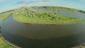 Quadrocopter, flies over the river enveloping a small island. There are many trees along the river. Summer sunny day. Video shooting from a bird`s-eye view stock video