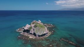 Quadrocopter is flying from high coast and moving to Mediterranean sea, over basalt rock. Turquoise water stock video footage