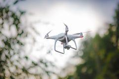 Quadrocopter que vuela blanco con la cámara en fondo verde del bosque imagenes de archivo