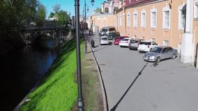 Quadrocopter shoot street with water channel in summer sunny day. Slow motion. Quadrocopter shoot street with water channel and people in summer sunny day. Slow stock video footage
