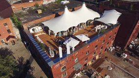 Quadrocopter shoot summer restaurant with white tents on roof building. Sunny day. Wedding ceremony stock video footage