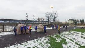 Quadrocopter shoot teens establish tents in field. Emercom training. Slow motion. Day stock footage