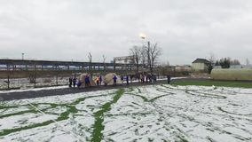 Quadrocopter shoot teens establish tents in snow stadium. Emercom training. Day stock video